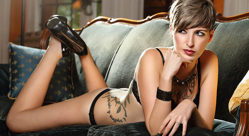 Sensual short hair model posing on a blue velvet sofa . Sexy and romantic concept