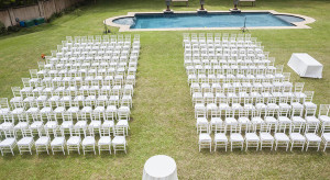 White chairs dozens positioned on grass lawn outdoors for private wedding occasion.