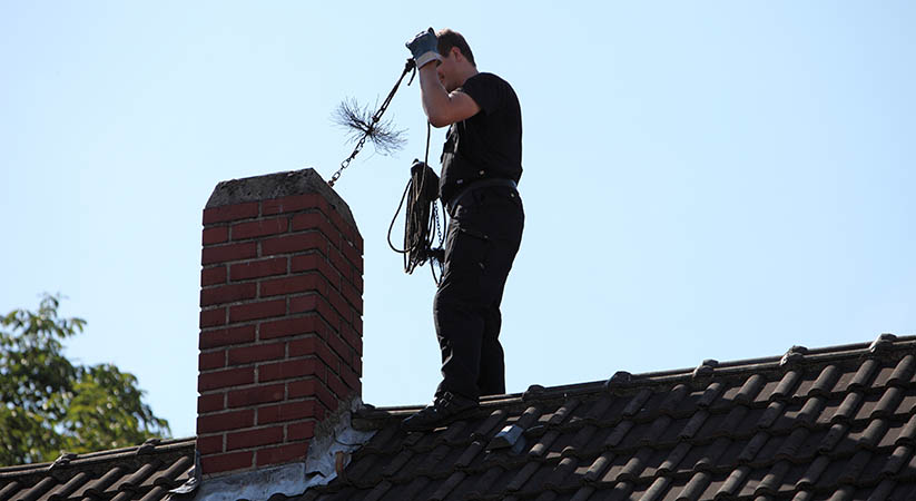 Chimney sweep inserting a coarse wire brush into the flue of a chimney while standing on top of the roof