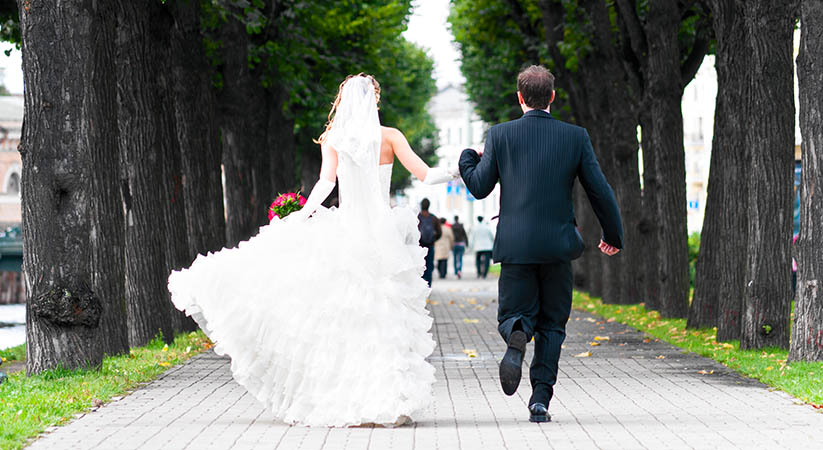 bride and groom is running with joined hands on city park road