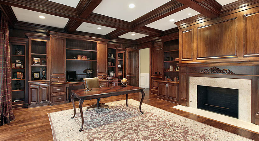 Library in luxury home with fireplace