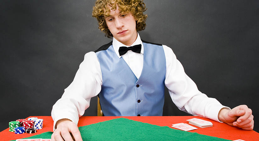 A casino dealer looking sadly at the cards on the table in front of him