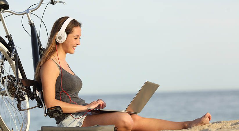 Teen girl studying with a laptop on the beach leaning on a bicycle