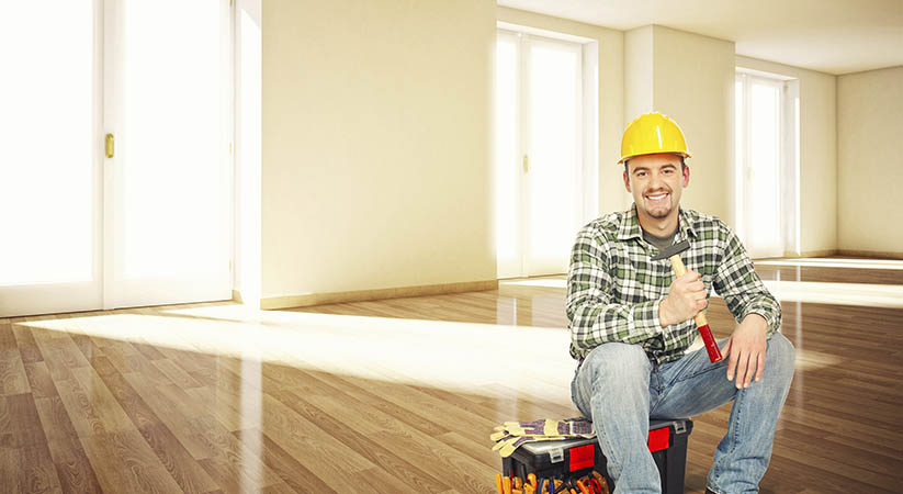 smiling worker sit in empty house